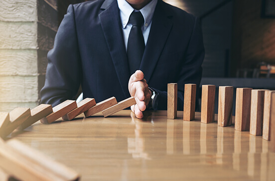 Businessman sitting at desk with dominoes using his hand to stop them from falling over