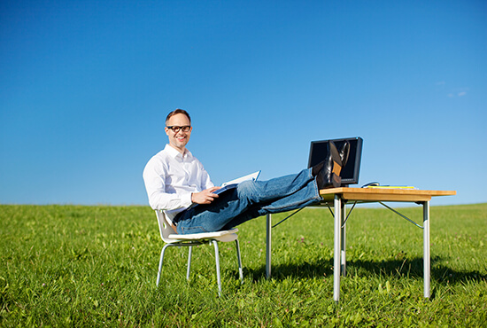 A businessman sitting in a chair in a grassy field with a desk and laptop, relaxing with his feet on the desk